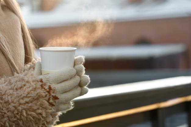 Femme mains dans des mitaines blanches tenant une tasse blanche fumante de café chaud ou de thé en froide journée ensoleillée d'hiver