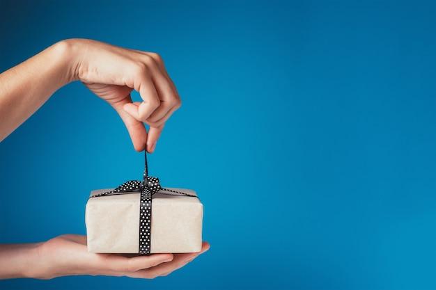 Femme mains déballage boîte cadeau avec archet