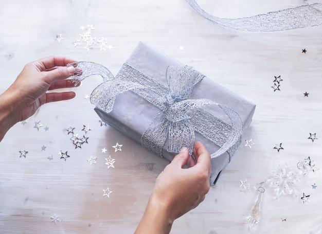 Femme mains emballage cadeau de noël avec arc en argent