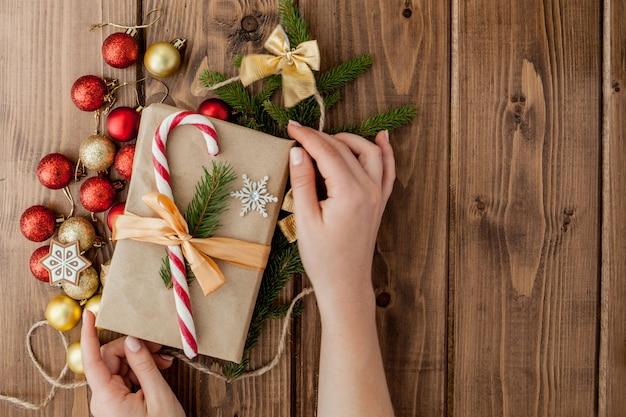 Femme, mains, emballage, cadeau noël, gros plan cadeaux de noël non préparés avec des éléments de décoration et des objets, vue de dessus. concept d'emballage de bricolage de noël ou du nouvel an.