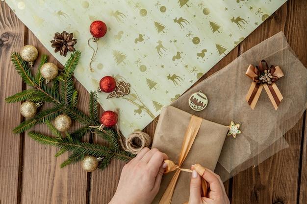 Femme, mains, emballage, cadeau noël, gros plan noël non préparé présente sur bois avec des éléments de décoration et des éléments, vue de dessus. emballage de bricolage de noël ou du nouvel an.