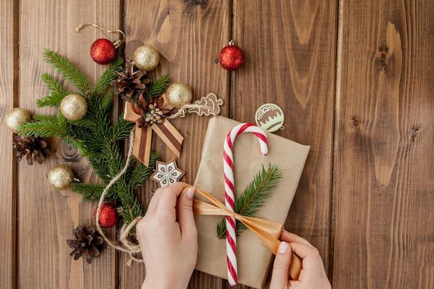 Femme, mains, emballage, cadeau noël, gros plan noël non préparé présente sur bois avec des éléments de décoration et des éléments, vue de dessus. emballage bricolage de noël ou du nouvel an.