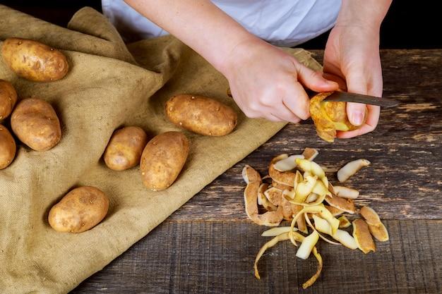 Femme mains épluchent des pommes de terre, épluchures sur une planche à découper en bois.