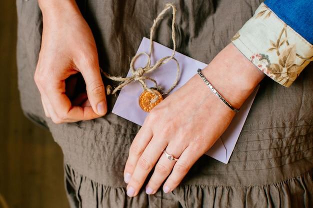 Femme, mains, genoux, tenue, enveloppe