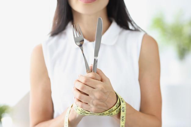 Femme avec les mains liées avec un ruban à mesurer tenant une fourchette et un couteau en gros plan