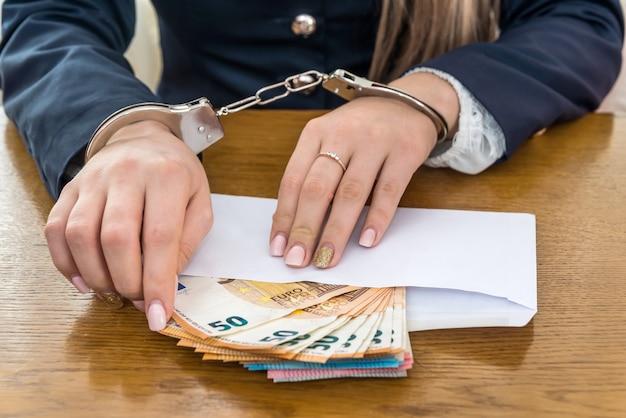 Femme mains menottes aux poignets avec des billets en euros dans une enveloppe