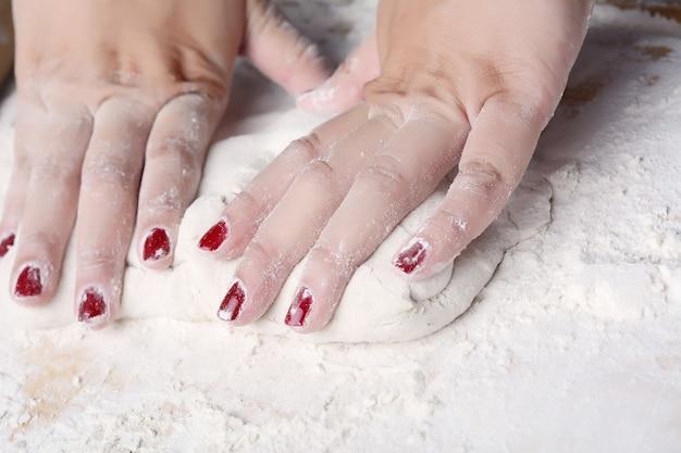 Femme mains pétrir la pâte.