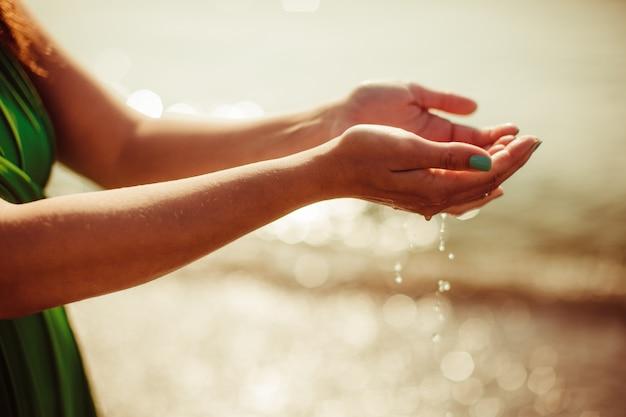 Femme avec les mains pleines d'eau