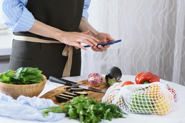 Femme, mains, à, smartphone, dans, cuisine, cuisson, légumes, cuisson, chez soi, concept