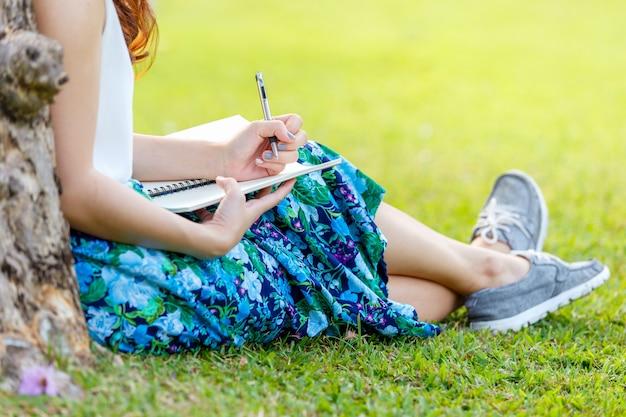 Femme, mains, stylo, écriture, cahier, herbe, dehors