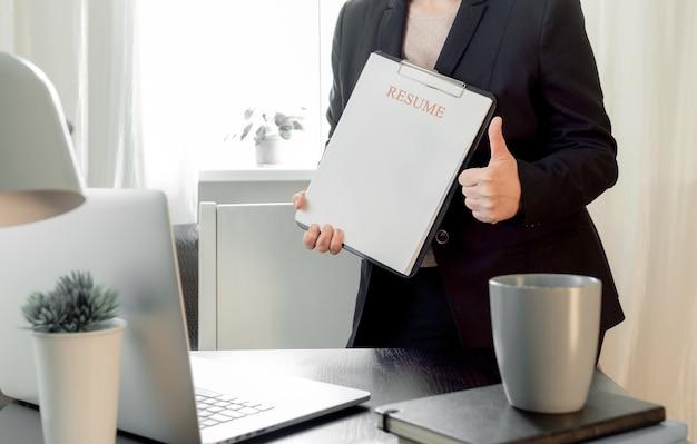 Femme mains tenant l'application de cv près de son lieu de travail avec ordinateur portable.