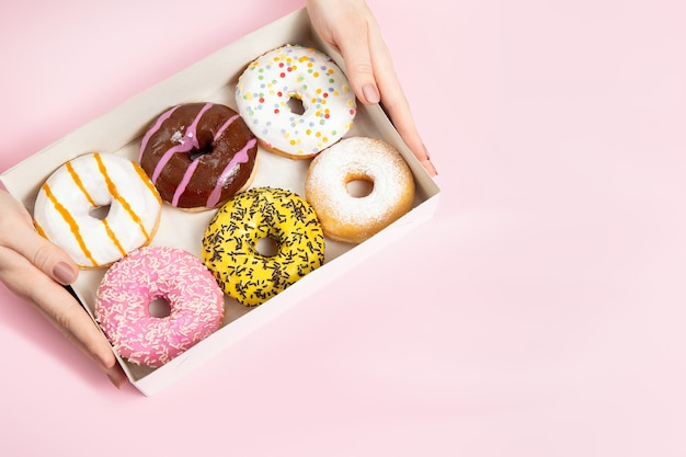 Femme mains tenant des beignets émaillés ronds colorés avec des paillettes de boîte à beignets sur une surface rose pastel