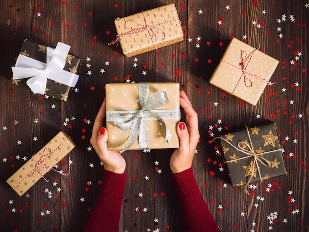 Femme mains tenant la boîte de cadeau de vacances de noël sur la table de fête décorée