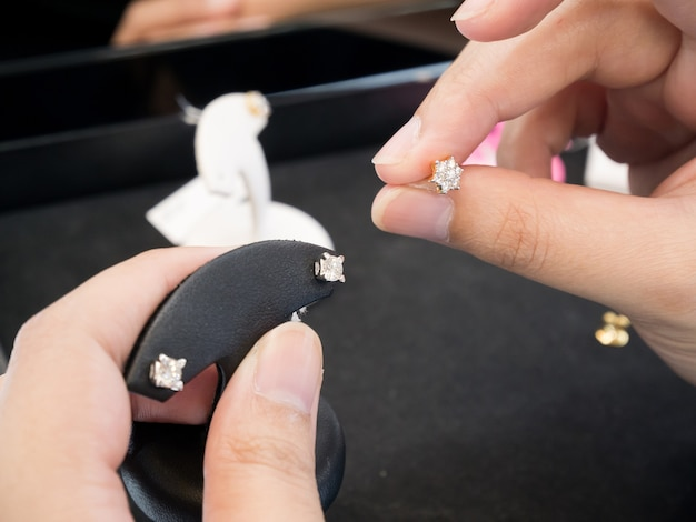 Femme mains tenant des boucles d'oreilles en diamant à la bijouterie en diamant