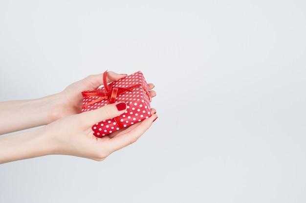 Femme mains tenant un cadeau rouge avec ruban, mains manucurées avec vernis à ongles sur blanc