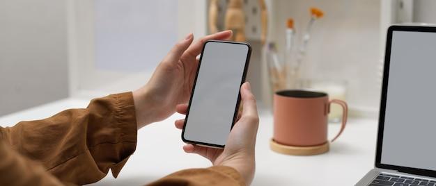 Femme mains tenant une maquette de smartphone alors qu'il était assis à la table de travail avec une maquette d'ordinateur portable au bureau à domicile