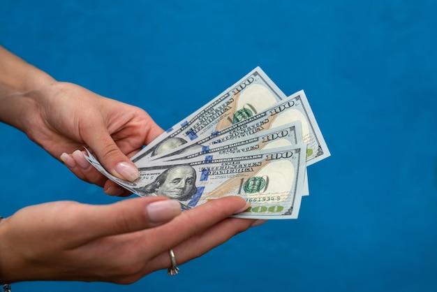 Femme mains tenant pile d'argent isolé sur mur bleu