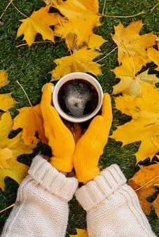Femme mains tenant une tasse de café à côté de feuilles d'érable jaune sur une herbe verte