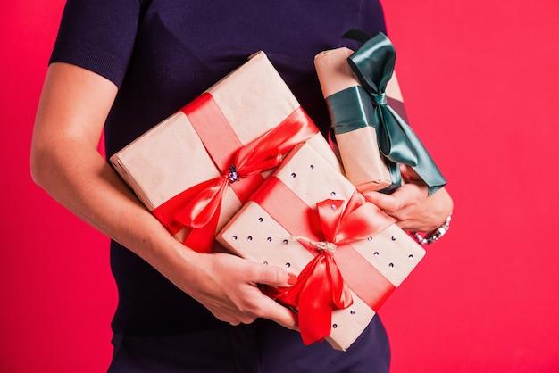 Femme mains tenant trois cadeaux au studio fond rose