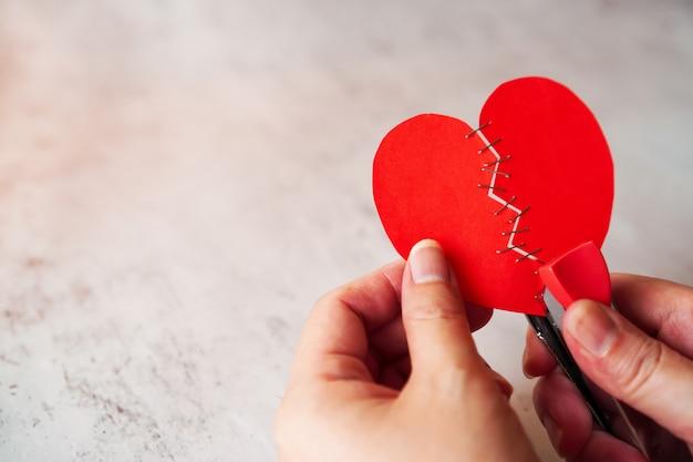 Femme, mains, tenir coeur brisé rouge, fixation, par, agrafeuse
