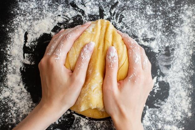 Femme mains tenir la pâte préparée sur le tableau noir