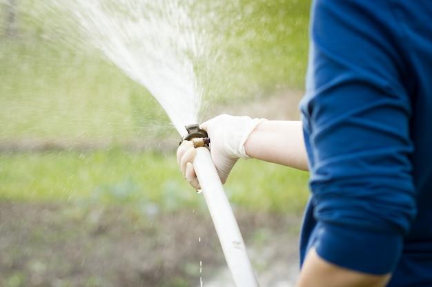Une femme les mains avec un tuyau d'arrosage arrosant son immense jardin pendant la belle période printemps / été; un dur travail; sénior; jardinage