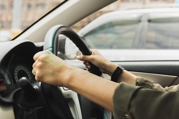 Femme mains sur le volant d'une voiture en conduisant sur la route.
