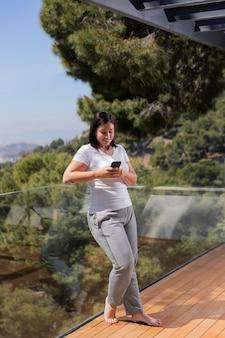 Femme à la maison à l'aide de mobile