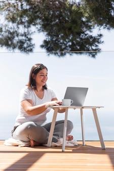 Femme à la maison à l'aide d'un ordinateur portable