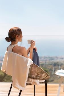Femme à la maison en appréciant une tasse de café