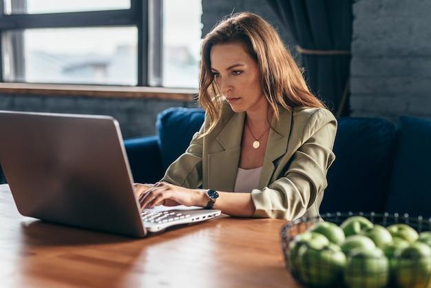 Femme à la maison assise au bureau avec ordinateur portable.