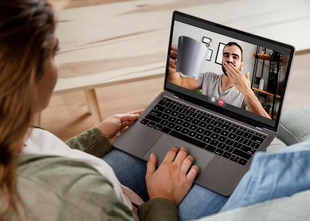 Femme à la maison ayant un appel vidéo sur ordinateur portable
