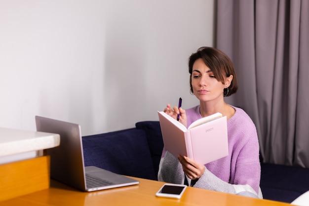 Femme à la maison avec un bloc-notes en pensant à des plans