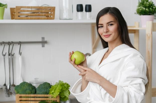 Femme sur la maison de la cuisine avec la cuisson des légumes verts. vitamines de régime alimentaire à domicile helthy jeune et belle femme. prise de vue en studio.
