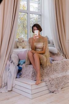 Femme à la maison dans la chambre à coucher portant une robe de noël du soir, prenant selfie photo