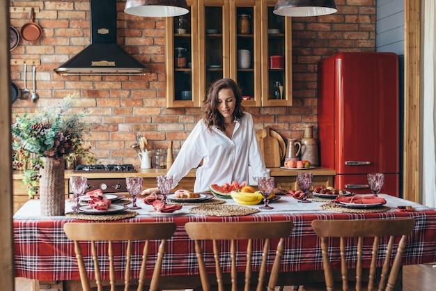 Femme à la maison dans la cuisine à table avec de la nourriture.