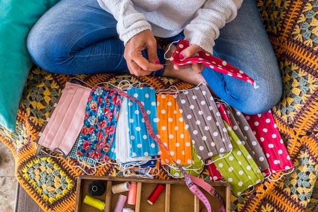 Femme à la maison faisant un masque médical facial coloré pour se protéger du virus