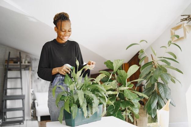 Femme à la maison. fille dans un pull noir. femme africaine au bureau. personne avec pot de fleurs.