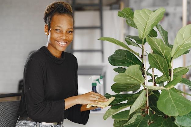 Femme à la maison. fille dans un pull noir. femme africaine utilise le chiffon. personne avec pot de fleurs.