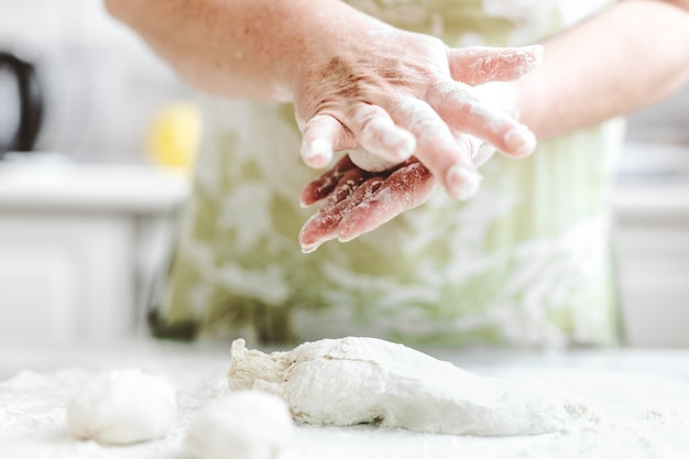 Femme à la maison, pétrir la pâte pour cuire des pâtes à pizza ou du pain. concept de cuisine maison. mode de vie