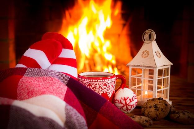 Femme à la maison. pieds dans des chaussettes de noël près de la cheminée. détente et confort. concept de vacances d'hiver