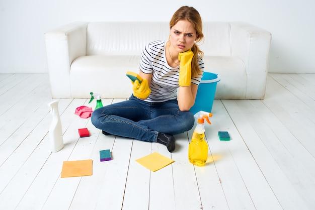 Femme à la maison près de canapé laver le sol