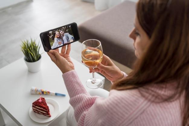 Femme à la maison en quarantaine, prendre un verre avec un ami sur smartphone