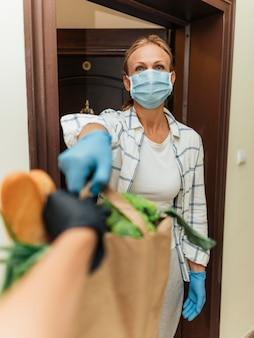 Femme à la maison ramassant ses courses en auto-isolement