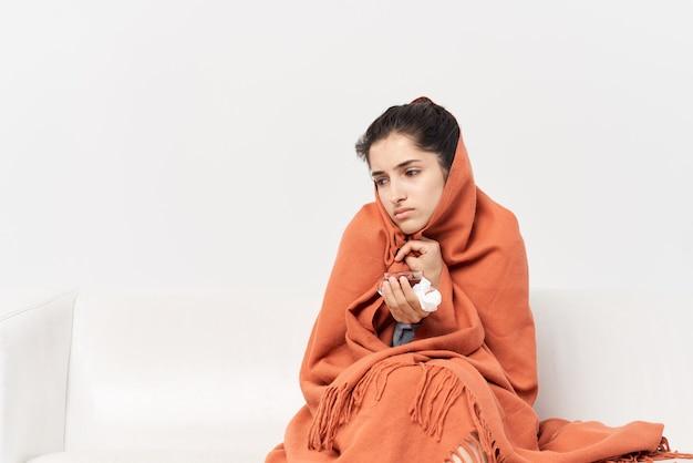 Femme à la maison avec une tasse de thé recouverte d'une couverture froide