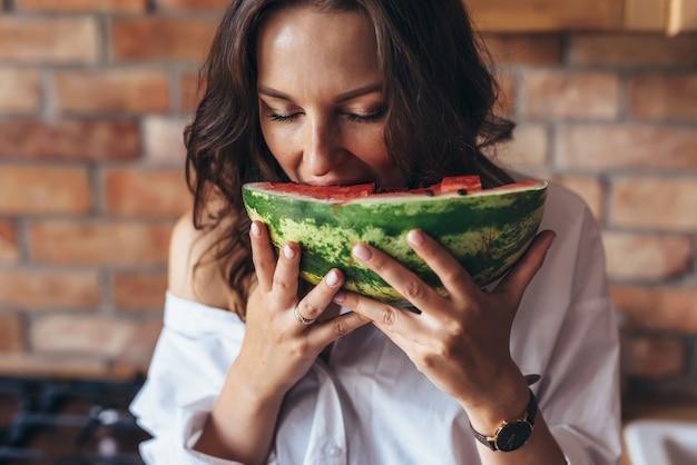 Femme à la maison en train de manger de la pastèque dans la cuisine.