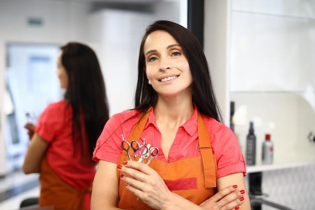 Femme maître coiffeur debout dans un salon de beauté et tenant des ciseaux