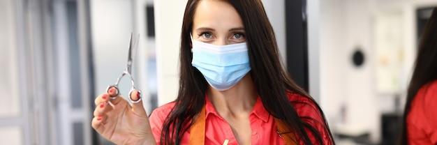 Femme maître coiffeur en masque médical de protection se trouve dans un salon de beauté et détient des ciseaux.