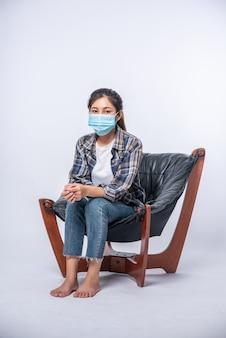 Une femme mal à l'aise assise sur une chaise et portant un masque