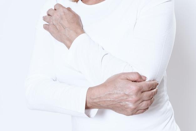 Une femme a mal au bras dans une pièce blanche.